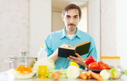 Portrait of man with cookbook in domestic kitchen Stock Photography