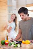 Portrait of a man cooking while his wife is washing the dishes Royalty Free Stock Photos