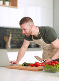 Portrait of man cooking vegetable in the kitchen while looking at a laptop computer on the table Royalty Free Stock Images