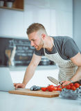 Portrait of man cooking vegetable in the kitchen while looking at a laptop computer on the table Stock Photo