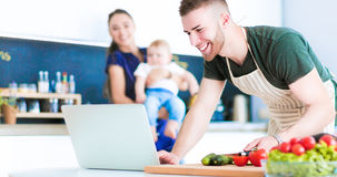Portrait of man cooking vegetable in the kitchen while looking at a laptop computer on the table Stock Photography