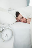Portrait of a man covering his ears while his alarm clock is rin Royalty Free Stock Image