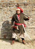Portrait of man with cutlass. Portrait of man in Cossack costume with cutlass standing in front of stone wall Stock Image