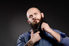 Portrait of  man cutting his beard with scissors and looking at camera Stock Photos