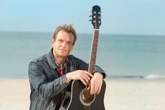 Portrait of man in a denim jacket near sea. Portrait of smiling man with acoustic. Outdoor shoot Royalty Free Stock Images