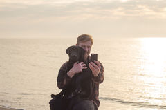 Portrait of man and dog make selfie on cellphone. Young caucasian male walking with dog on the morning beach, sunset on the sea or ocean and man with black Stock Photo