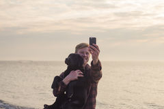 Portrait of man and dog make selfie on cellphone. Young caucasian male walking with dog on the morning beach, sunset on the sea or ocean and man with black Stock Image