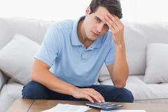 Portrait of a man doing his accounts. Portrait of an anxious man doing his accounts stock photo