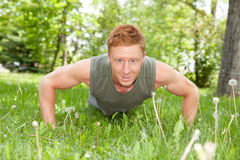 Portrait of man doing a push up. An attractive Caucasian man doing a push up outdoors Stock Photos