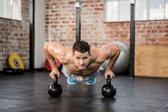 Portrait of man doing push ups with kettlebell Royalty Free Stock Image