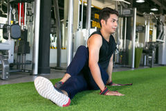 Portrait of a man doing stretching exercises at gym. Royalty Free Stock Images