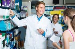 Portrait of man druggist in white coat giving advice to customer. Portrait of glad men druggist in white coat giving advice to customers in pharmacy Royalty Free Stock Image