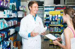 Portrait of man druggist in white coat giving advice to customer. Portrait of glad russian  men druggist in white coat giving advice to customers in pharmacy Royalty Free Stock Image