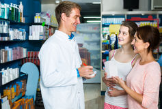 Portrait of man druggist in white coat giving advice to customer. Portrait of posiive  men druggist in white coat giving advice to customers in pharmacy Royalty Free Stock Images