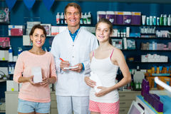 Portrait of man druggist in white coat giving advice to customer. Portrait of positive american men druggist in white coat giving advice to customers in pharmacy Stock Image