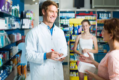 Portrait of man druggist in white coat giving advice to customer. Portrait of smiling russian men druggist in white coat giving advice to customers in pharmacy Royalty Free Stock Images