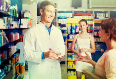 Portrait of man druggist in white coat giving advice to customer. Portrait of smiling russian men druggist in white coat giving advice to customers in pharmacy Royalty Free Stock Photo