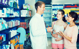 Portrait of man druggist in white coat giving advice to customer. Portrait of spanish smiling men druggist in white coat giving advice to customers in pharmacy Royalty Free Stock Image