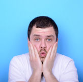 Portrait of man with dusgusted gesture against blue background Stock Photography