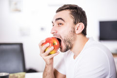 Portrait of a man eating an apple in the kitchen Royalty Free Stock Photo