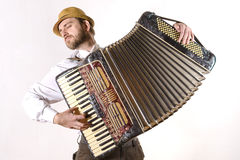 Portrait of a man emotionally playing the accordion. Portrait of a man wearing a straw hat and a white shirt emotionally playing the accordion Royalty Free Stock Photo