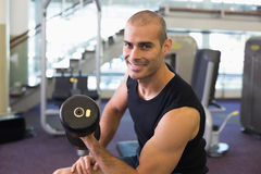 Portrait of man exercising with dumbbell in gym Royalty Free Stock Image