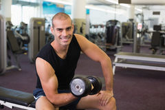 Portrait of man exercising with dumbbell in gym Stock Photo