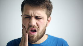 Portrait of a man experiencing toothache. Close up