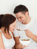 Portrait of a man feeding cereal to his wife Royalty Free Stock Images