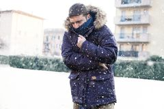 Portrait of man feeling very cold under snowy weather Royalty Free Stock Photo