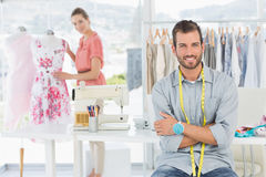 Portrait of man with female fashion designer working at studio. Portrait of a young men with female fashion designer working in background at the studio Royalty Free Stock Photo