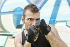 Portrait of  man fighter in boxing pose, urban style. Royalty Free Stock Images