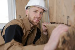 Portrait man fitting insulation into walls. Portrait of man fitting insulation into walls Royalty Free Stock Photography