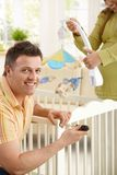 Portrait of man fixing baby bed Royalty Free Stock Images