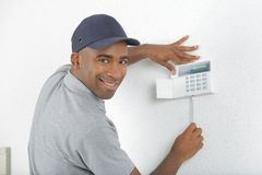 Portrait man fixing keypad to wall. Portrait of man fixing keypad to wall Royalty Free Stock Photography