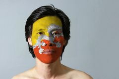 Portrait of a man with the flag of the Bhutan painted on his face on grey background. Triangle yellow and orange with white dragon stock photos