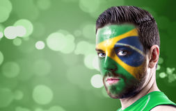 Portrait of a man with the flag of the Brazil painted on his face Stock Image