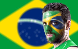 Portrait of a man with the flag of the Brazil painted on his face Royalty Free Stock Photo