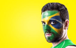 Portrait of a man with the flag of the Brazil painted on his face.  Stock Photo