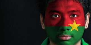 Portrait of a man with the flag of the Burkina Faso painted on his face on black background. Portrait of a man with the flag of the Burkina Faso painted on his stock photos