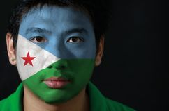 Portrait of a man with the flag of the Djibouti painted on his face on black background. Portrait of a man with the flag of the Djibouti painted on his face on royalty free stock photo