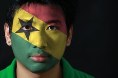 Portrait of a man with the flag of the Ghana painted on his face on black background. Portrait of a man with the flag of the Ghana painted on his face on black stock photos