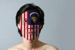 Portrait of a man with the flag of the Malaysia painted on his face on black background. Blue red white and yellow color with yellow star and white Crescent royalty free stock photos