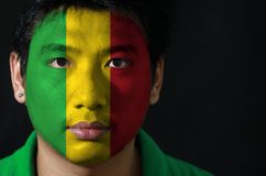 Portrait of a man with the flag of the Mali painted on his face on black background. Portrait of a man with the flag of the Mali painted on his face on black stock photography