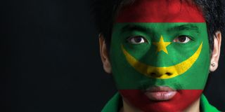 Portrait of a man with the flag of the Mauritania painted on his face on black background. The concept of sport or nationalism. two red stripes flanking a royalty free stock image