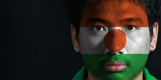 Portrait of a man with the flag of the Niger painted on his face on black background. The concept of sport or nationalism. orange white and green; charged with stock photo