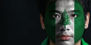 Portrait of a man with the flag of the Norfolk Island painted on his face on black background. The concept of sport or nationalism royalty free stock images
