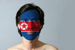 Portrait of a man with the flag of the North Korea painted on his face on black background. Horizontal red white and blue, red star within a white circle stock image