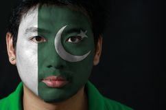 Portrait of a man with the flag of the Pakistan painted on his face on black background. The concept of sport or nationalism. a white star and crescent on a stock photo