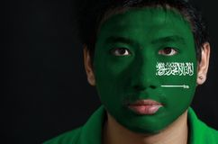 Portrait of a man with the flag of the Saudi Arabia painted on his face on black background. stock photos